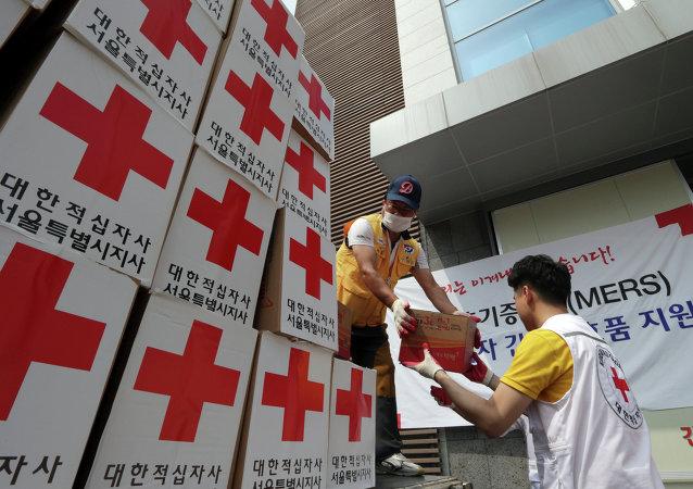 Los miembros de la Cruz Roja de Corea del Sur descargan  un camión con ayuda para las personas que se sospecha de la infección