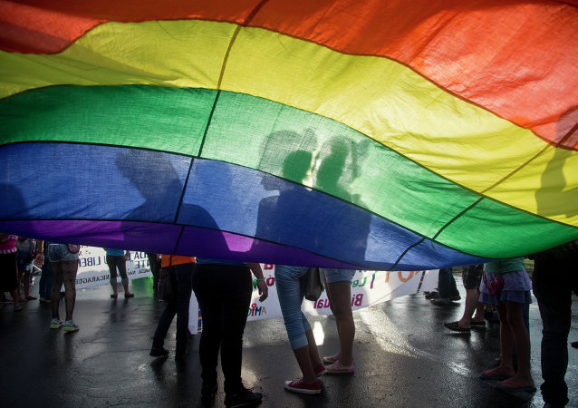 Members of the LGBT movement hold a gay pride flag as they attend a march to mark the International Day Against Homophobia in Managua, Nicaragua, Sunday, May 17, 2015.