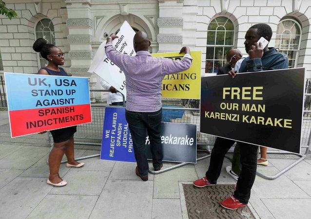 Manifestantes sostienen carteles exigiendo la liberación de jefe de inteligencia de Ruanda Karenzi Karake en Londres