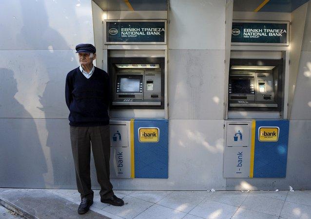 Jubilado espera al lado de un cajero automático del Banco Nacional de Grecia para percibir su pensión en Tesalónica, Grecia, el 29 de junio, 2015