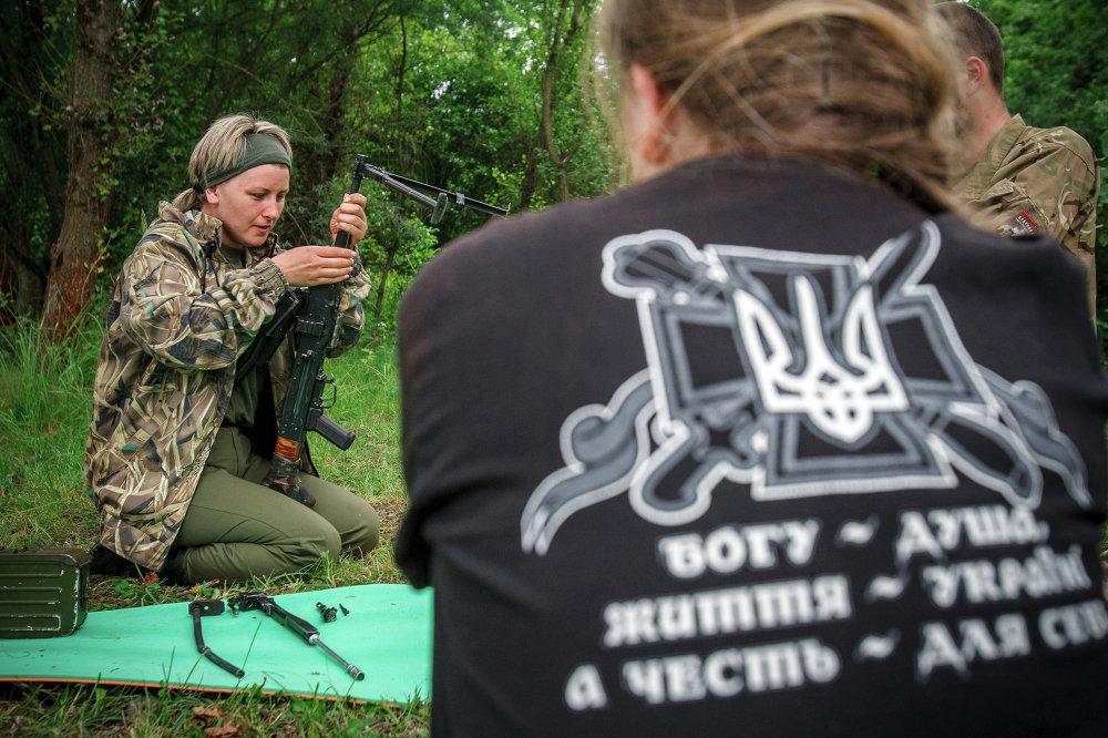 """Una combatiente de la centuria femenina de Pravy Sektor examina una ametralladora mientras le observa su compañera que lleva una camiseta que dice """"El alma al Dios, la vida a Ucrania, el honor para mí"""""""