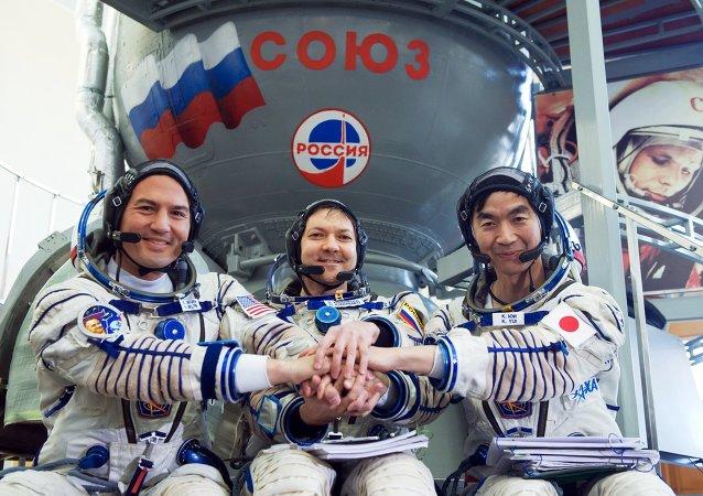 Tripulación de EEI-44/45 al lado de cohete Soyuz