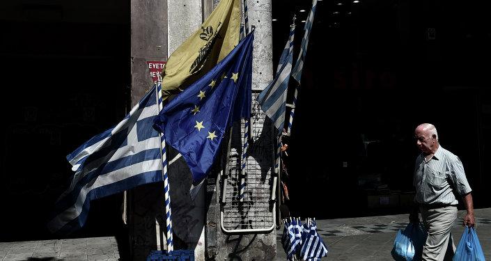 Un hombre camina delante de las banderas de UE y Grecia en el centro de Atenas. 13 de julio de 2015