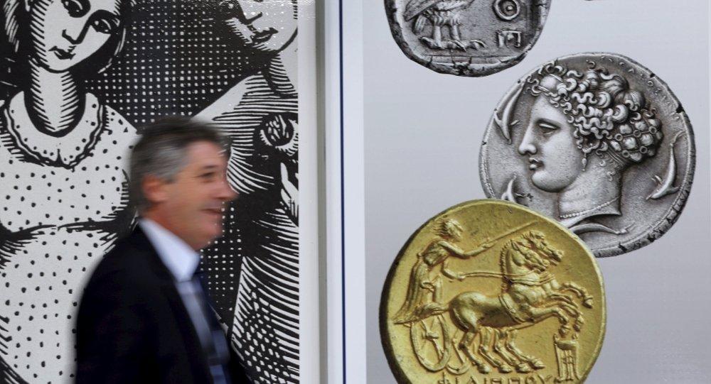 Un hombre camina delante de las monedas en el centro de Atenas, el 13 de julio, 2015