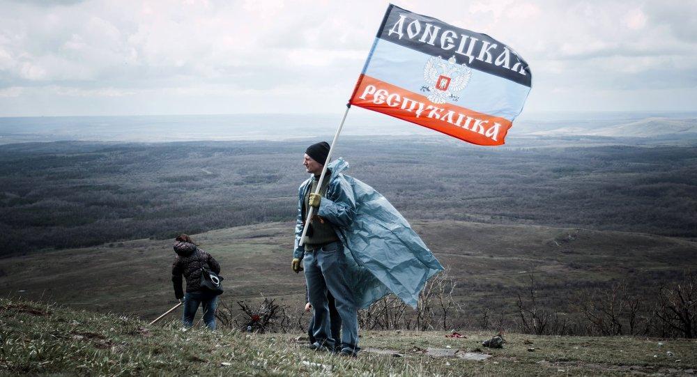 Hombre con la bandera de la RPD cerca el monumento de Saur Moguila en Donetsk, Ucrania