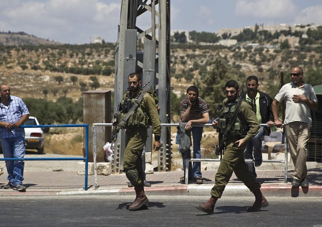 Israeli soldiers walk towards an Israeli checkpoint near the West Bank town of Bethlehem, after a stabbing attack