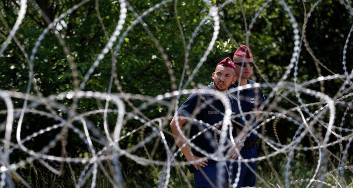 Policías húngaros guardan una valla contra migrantes