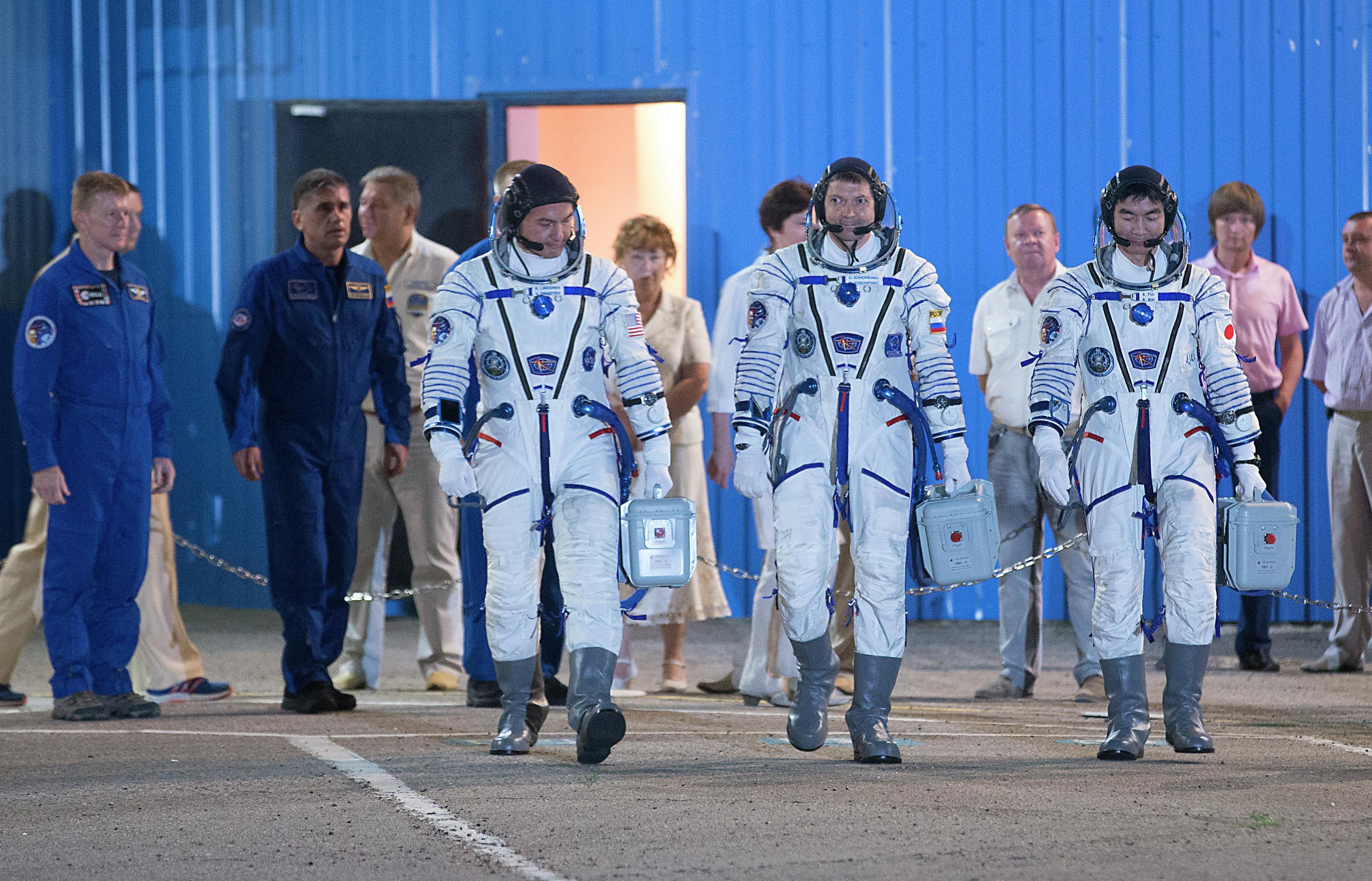 Los miembros de la tripulación de la nave Soyuz TMA-17M: Kjell Lindgren (izda.), Oleg Kononenko (centro) y Kimiya Yui (dcha.)