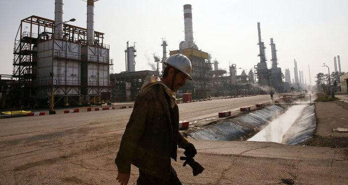 Trabajador petrolero iraní camina cerca una refinería de petróleo en Teherán, Irán (imagen referencial)