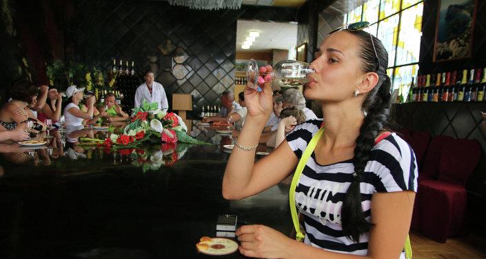 Mujer bebe vino en Crimea