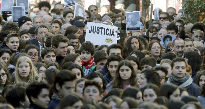 Manifestantes con fotos de víctimas de ataque a la AMIA durante un mítin en conmemoración de 21º aniversario de atentado en Buenos Aires, Argentina