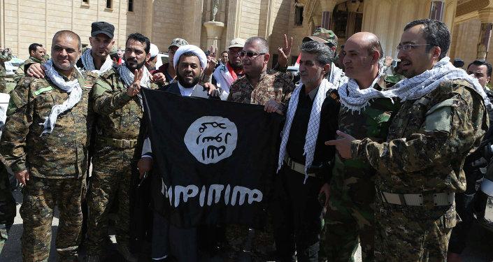 Fuerzas de Movilización Popular de Irak con la bandera del EI en Tikrit