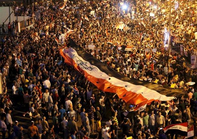 Iraquíes llevan la bandera nacional durante manifestación
