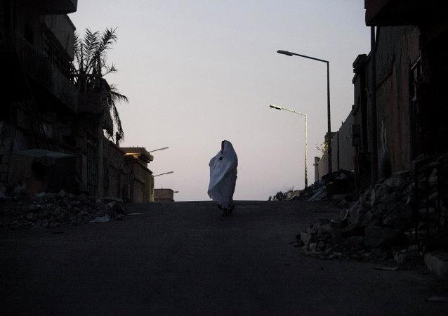 Una mujer libia va por las ruinas en Sirte, Libia, El 16 de julio del 2012.