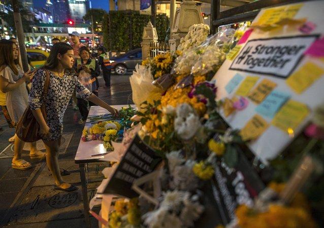 Una mujer pone flores a santuario Erawan donde occurió el atentado este lunes