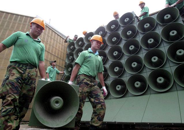 Soldados de ejército surcoreano llevan las altavoces que transmiten propaganda