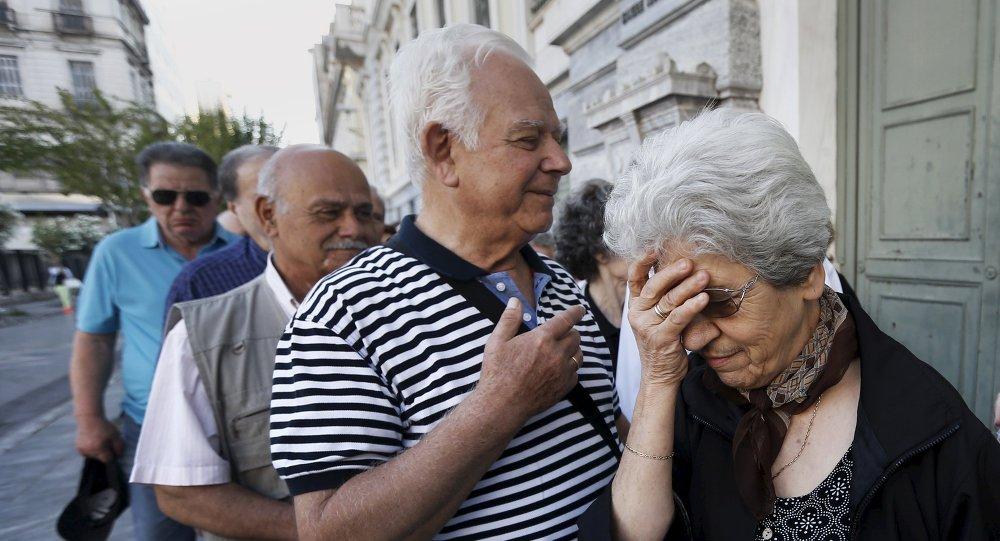 Pensionistas griegos hacen cola en un banco en Atenas