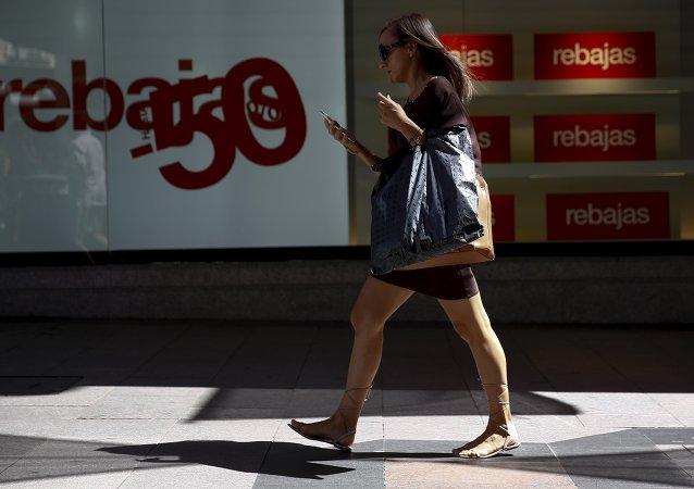 Una mujer pasa cerca una tienda