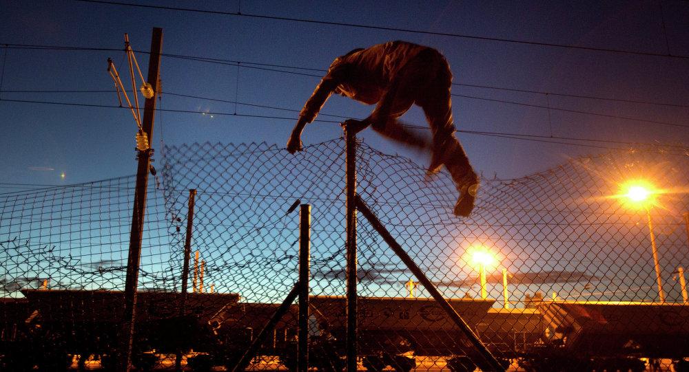 Inmigrante intenta llegar a Eurotúnel en Calais, Francia