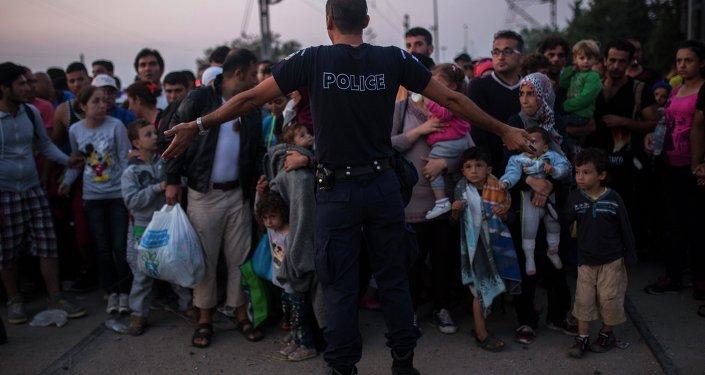 Policía griego ordena a los refugiados sirios mientras ellos preparan para cruzar la frontera con Macedinia