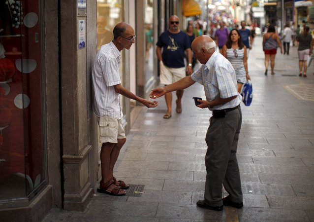 Un hombre da limosna a un mendigo en la ciudad de Ronda, España