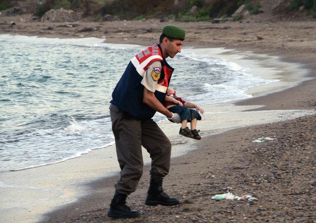 Un oficial de la policía paramilitar lleva el cuerpo sin vida de Aylan Kurdi