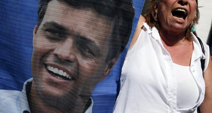 Participante de las manifestaciones con un retrato de Leopoldo López (archivo)
