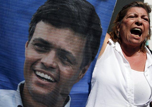 Participante de las manifestaciones con un retrato de Leopoldo López