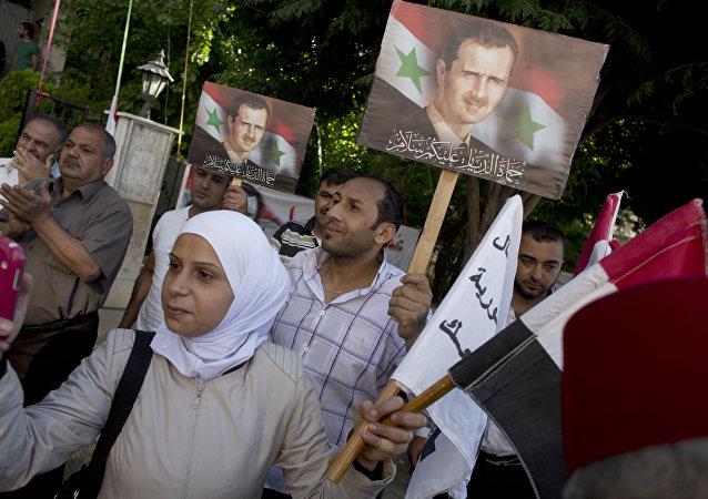 La gente tiene retratos del presidente sirio Bashar Assad fuera de un centro de votación en Damasco