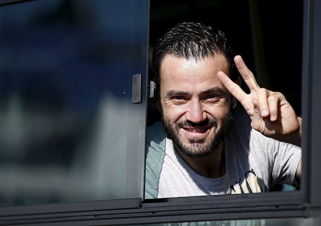 Refugiado desde Siria muestra una seña de victoria al arribar en el puerto de Piraus, Grecia
