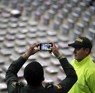 Policíaco toma fotos de paquetes de cocaína presentados por la Policía para la prensa en Bogota, Colombia