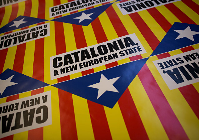 "In this photo taken on Tuesday, Nov. 13, 2012, flags for sale that combines the slogan of EU aspiration with the red-and-yellow stripes, blue triangle and white star of the ""estelada"" flag that symbolizes Catalonia's independence drive are laid out in a printing shop in Girona, Spain."
