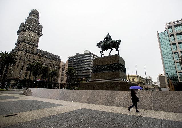 Una persona camina en la vacía Plaza de la Independencia en el centro de Montevideo durante una huelga de 24 horas en reclamo de aumentos salariales