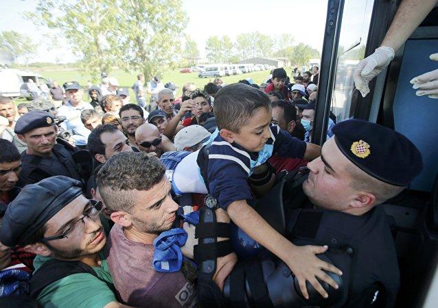 Policía croata ayuda a un niño de refugiado a subirse al autobús en Tovarnik, Croacia