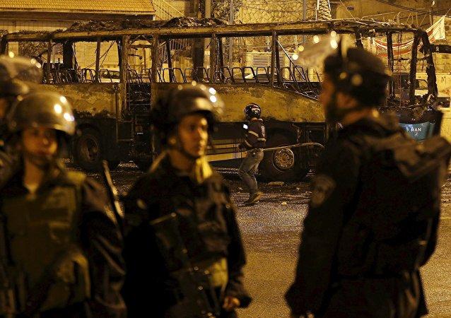 Policíacos de la Guardia Fronteriza de Israel cerca de un autobús derrotado por los protestantes palestinos, Jerusalén Este