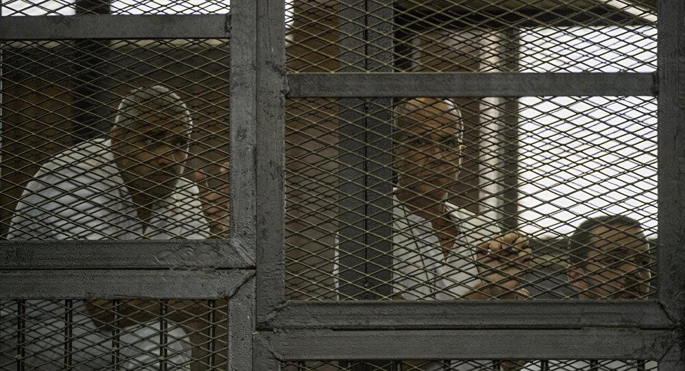 Periodista de la cadena Al-Jazeera Peter Greste (centro), periodista egipcio-canadiense Mohamed Fahmi (izda.) y periodista egipcio Mohamed Baher durante la audiencia tribunal, Egipto
