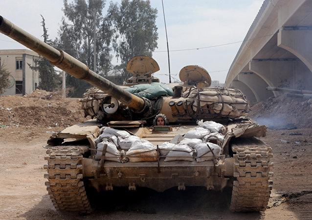 Una soldado del ejército sirio en un tanque en afueras de Damasco
