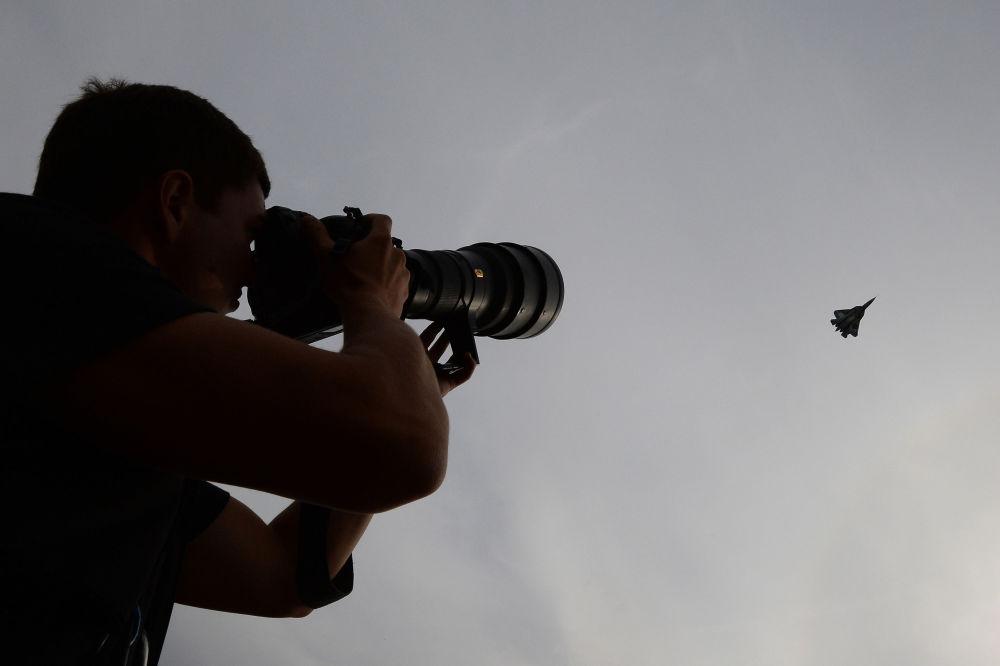 Un hombre sigue la exhibición de vuelo del T-50 durante el salón aeroespacial internacional MAKS 2013 en Zhukovski