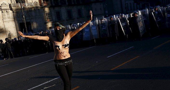 Una manifestante hace gestos frente a la policía antidisturbios durante los enfrentamientos con la policía antidisturbios en una marcha por el aniversario de la masacre de la plaza Tlatelolco en 1968