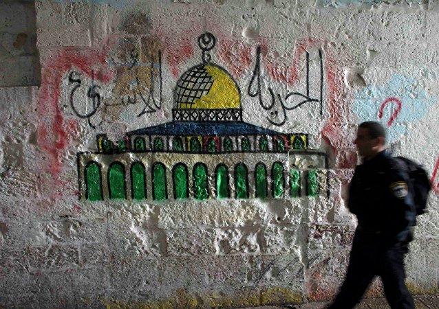 Un policíaco de Israel pasa por el muro con la imagen de la Cúpula de la Roca, Jerusalén