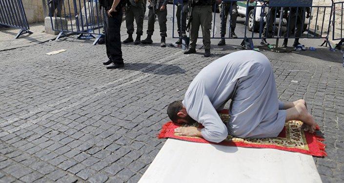 Un palestino reza afuera de la Ciudad Vieja de Jerusalén