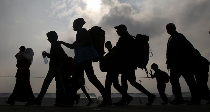 Migrants are silhouetted against the sky as they make their way to board buses in Nickelsdorf, Austria, October 6, 2015
