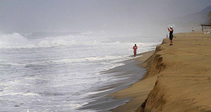 Un hombre toma fotografías de las olas en la playa de Acapulco, México (archivo)