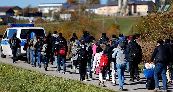 Policía local escolta a un grupo de refugiados despues de cruzar frontera austro-alemana