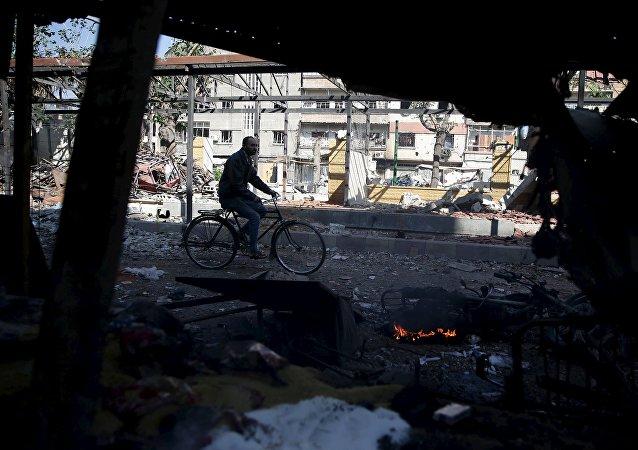 Un hombre en bicicleta en Douma, un barrio a las afueras de Damasco