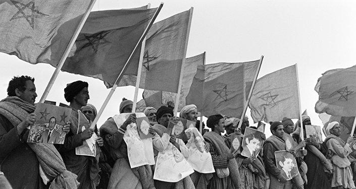 Marroquiés con los retratos del rey Hasan II, textos del Corán y banderas de Marruecos en la Marcha Verde