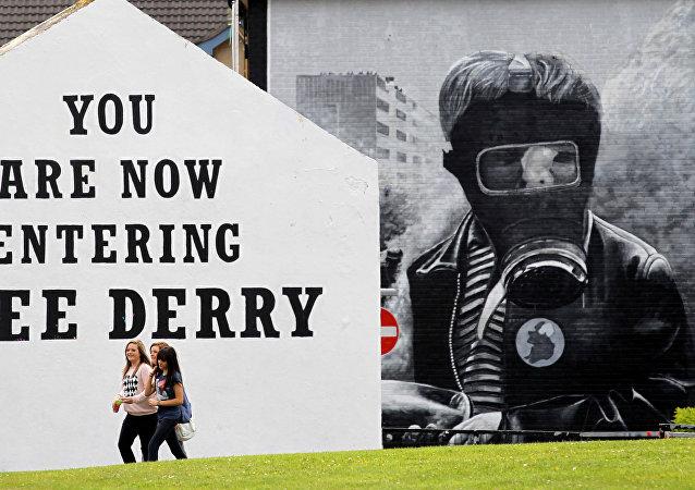Niñas pasan junto a un mural 'Domingo Sangriento' en el área de Bogside de Londonderry, Irlanda del Norte