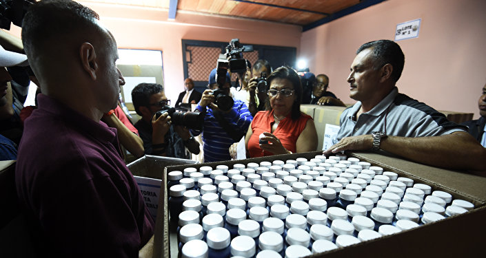Empleados del CNE muestran la tinta indeleble que se utilizará para marcar los votantes en los colegios electorales