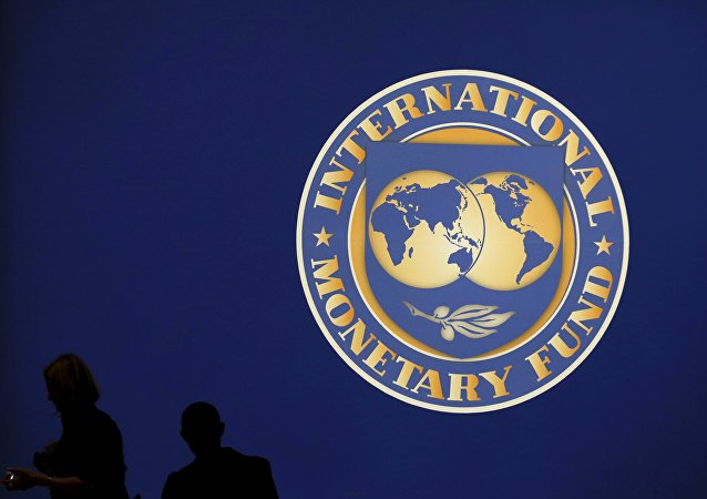 Visitors are silhouetted against the logo of the International Monetary Fund at the main venue for the IMF and World Bank annual meeting in Tokyo in this October 10, 2012