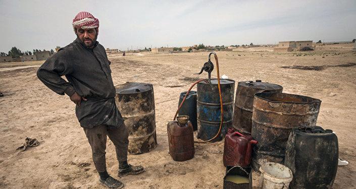 Un hombre trabaja en una refinería de petróleo improvisada en Raqqa, Siria